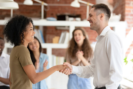 Happy african female intern worker getting hired promoted handshaking caucasian boss congratulating successful black employee by shaking clapping hand give reward bonus, gratitude recognition concept