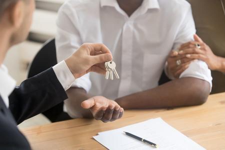 Immobilienmakler, der die Schlüssel an schwarze Pärchenmieter hält, afrikanische Familienkunden machen das Geschäft zum Erstbesitzer, Hypothek, Eigentumskonzept, Hände aus nächster Nähe Standard-Bild