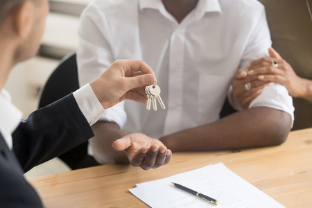 Real estate agent realtor holding giving keys to black couple renters tenants, african family customers make deal become first time owners, mortgage, property ownership concept, hands close up view Imagens