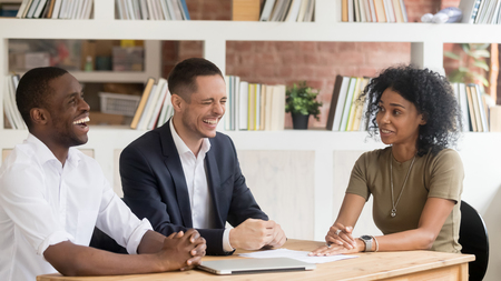 Happy diverse hr managers laughing at funny joke listen to african female applicant at job interview, winning black candidate make good positive first impression on recruiters during hiring process