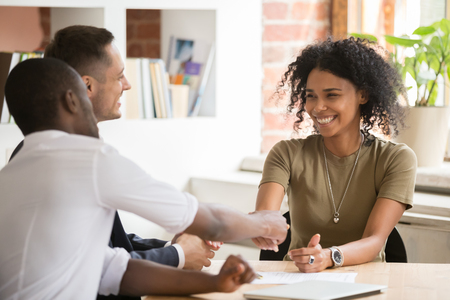 Happy female african vacancy candidate shaking hand of hr recruiting manager congratulating hired applicant with handshake, successful interview winner make good first impression got new job concept Banco de Imagens