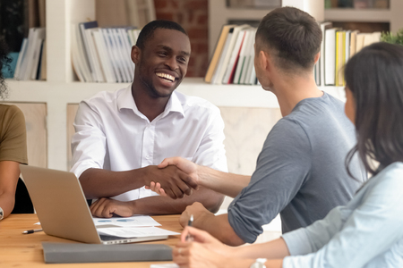 Happy african black businessman handshaking white partner congratulating with successful deal thank for help introducing get acquainted, diverse employees shake hands greeting at office group meeting
