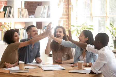Happy multi ethnic creative business startup team associates group join hands giving high five together celebrate success teamwork, corporate vision teambuilding, connection participation concept