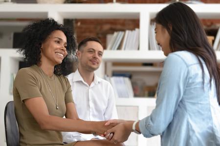 Donne asiatiche e africane che si tengono per mano durante la sessione di terapia di gruppo, diversi amici che provano sollievo riconciliato sorridendo dando supporto psicologico empatia superando il problema durante la consulenza psicoterapeutica Archivio Fotografico