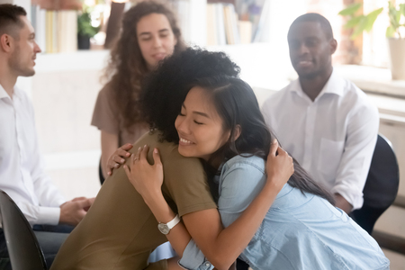 Asiatische und afrikanische Frauen, die während der Gruppentherapie-Beratungssitzung psychologische Unterstützung leisten, verschiedene Damen umarmen sich im Kreis und fühlen sich erleichtert, Empathie, die einem Freund bei Problemen hilft