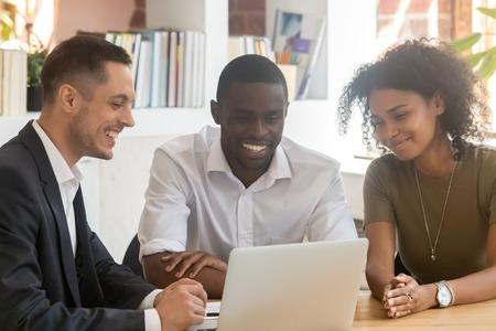 Agente hipotecario de seguros vendedor que consulta pareja africana que muestra una presentación en línea en una computadora portátil en la oficina, asesor financiero que hace una oferta a los jóvenes clientes negros que miran la computadora Foto de archivo