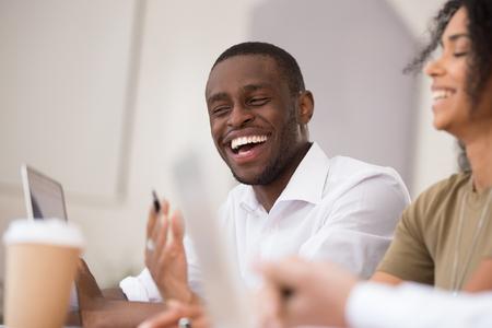 Felice uomo d'affari afroamericano che ride parlando lavorando insieme a colleghi amichevoli, sorridente uomo di colore millenario che si diverte conversazione di squadra scherzando con i colleghi durante la pausa in ufficio