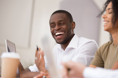Happy african american businessman laughing talking working together with friendly colleagues, smiling millennial black man having fun team conversation joking with coworkers during office break Foto de archivo - 118050182