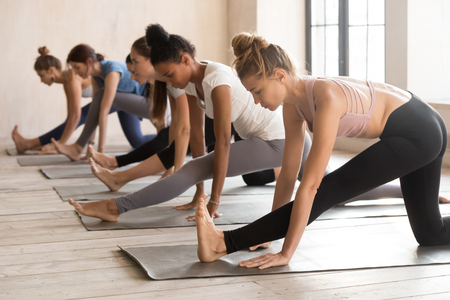 Group of young diverse sporty people doing yoga Half splits exercise, Ardha Hanumanasana pose, mixed race female students training atdoor at club sport or studio. Well being, wellness concept