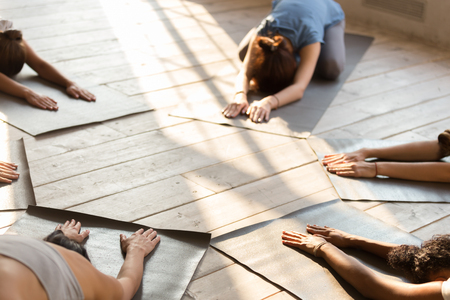 Group of diverse young sporty people at yoga lesson, doing Child exercise, Balasana pose, mixed race female students training indoor at club or studio. Well being, wellness concept, close up. Top view