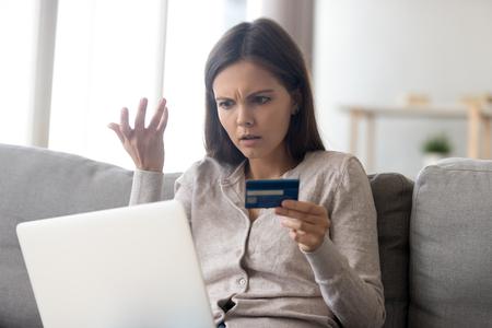 Mujer joven molesta que usa el servicio de banca en línea, problema con la tarjeta de crédito bloqueada, que usa la computadora portátil, niña irritada que controla el saldo, concepto de fraude en Internet, quiebra o deuda, gasto excesivo Foto de archivo