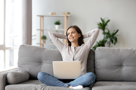 Happy woman stretching hands, relaxing on cozy sofa with laptop in living room at home, smiling girl resting after finished computer work, dreaming, thinking about good future, break Imagens