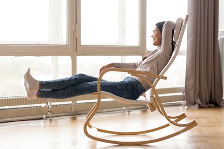 Smiling woman relaxing in comfortable rocking chair at home, looking out big window, happy cheerful girl resting with stretched legs, dreaming about good future, enjoying free time, weekend