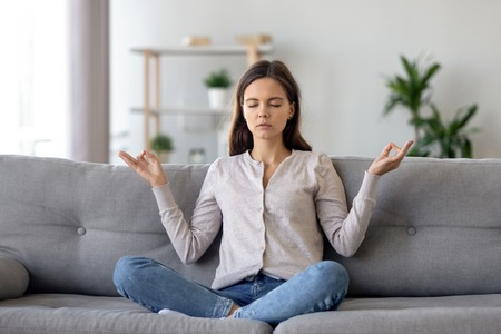 Peaceful young woman sitting in lotus pose on sofa in living room, meditating, attractive girl with closed eyes practicing yoga at home, stress relief concept, healthy good habit
