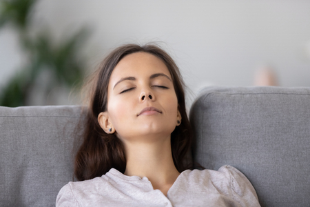 Calm young woman relaxing on comfortable sofa with closed eyes, close up, peaceful girl sleeping, enjoying weekend, resting at home, breathing deep, leaning back on couch in living room