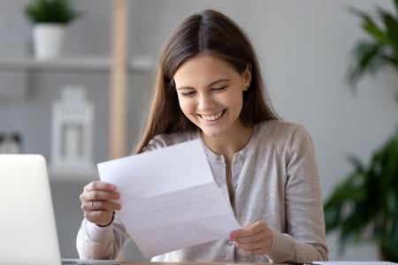 Glimlachende gelukkige studente of werknemer die goed nieuws leest in een papieren brief, aan een bureau zit met laptop, geweldige baanaanbieding ontvangt, examenresultaten succesvol, document in handen houden, veel