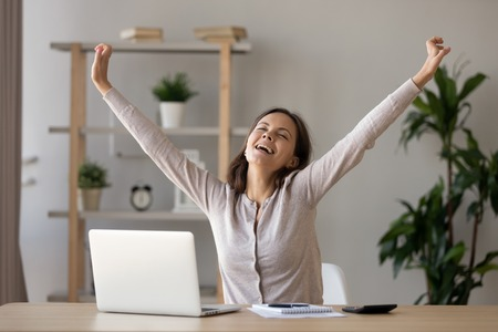Excited smiling woman with closed eyes stretching hands at workplace after finish work, relaxing, doing easy exercise during break, happy girl enjoying free time, celebrating success