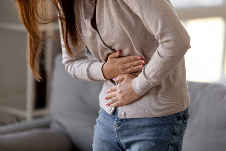 Close up woman holding belly, feeling discomfort, health problem concept, unhappy girl standing at home, suffering from stomachache, food poisoning, gastritis, abdominal pain, menstrual period Banque d'images