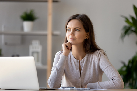 Thoughtful attractive woman planning, thinking about strategy in office, dreamy girl sitting at desk, working on project, using laptop, dreaming about success, good future, positive visualization
