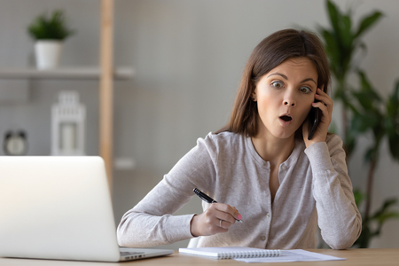 Shocked woman talking on phone, hearing amazing unexpected news, writing notes, surprised worker with open mouth listening to caller, answering call, chatting, gossiping with friend during break