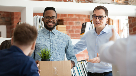 Black man having first working day getting acquainted with colleagues standing in office in front of workmates. Boss introducing employee, newcomer holds box with belongings starting career in company 写真素材
