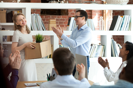 Diverse multinational staff clapping hands welcoming new employee gathered together in office room. Attractive woman holding carton box with belongings, having first working day in company feels happy Stock Photo - 118054278