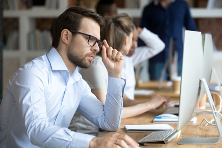 In coworking office working millennial diverse businesspeople, focus on confident serious man in glasses sitting at desk read business message surfing internet communicating online using corporate pc Stock Photo