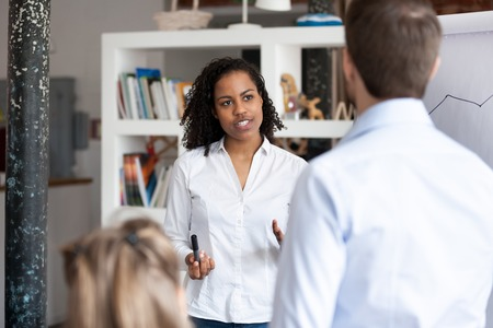 Male and female colleagues rear view, businesspeople listening black business coach gathered together for studying at modern office boardroom. Confident mixed race trainer studying company employees