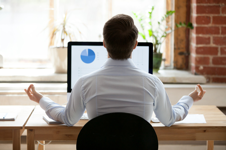 Rear back view businessman sitting at desk opposite pc doing yoga feels placidity and calmness. Employee take break resting relaxing practicing meditation. Healthy lifestyle and stress relief concept Stock Photo