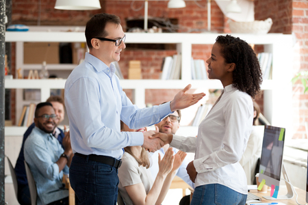 Ceo handshaking with young mixed race african female congratulating successful worker with promotion, appreciating for good work result. Employee getting praise from boss while colleagues applauding