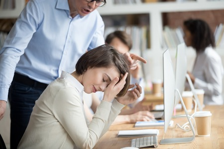 Angry irritated company boss reprimanding employee female, accusing of serious mistake and bad work. Young crying woman worker listening yelling from executive manager feels guilty frustrated unhappy Stock Photo