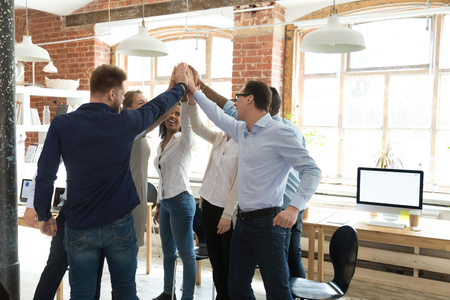 Happy multinational colleagues diverse business people standing in modern office giving high five holding hands together celebrating great results in common business. Togetherness and success concept