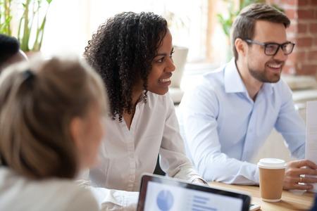 Schwarzafrikanischer Teamleiter Executive Manager, der am Schreibtisch im Konferenzraum sitzt, umgeben von verschiedenen Kollegen des Unternehmens bei Geschäftstreffen oder morgendlichen Briefing, teilt Informationen mit einem guten Gefühl.