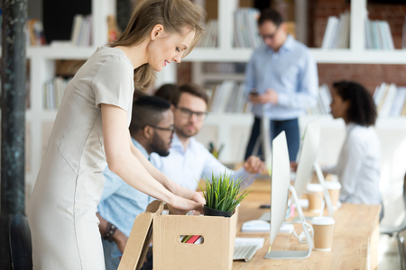 Positive hired female company employee unpacking box with personal belongings at workplace on first working day in coworking office, attractive newcomer woman getting new job feels excited and happy Stock Photo - 118054464