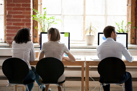 Three diverse multi-ethnic businesspeople, two females working together and male separately using computers sitting on chairs in shared contemporary comfortable light office, workmates rear back view