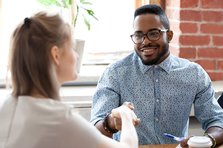 Confident positive mixed race black executive shaking hands greeting company partner before negotiating. Human resource manager before starting job interview handshaking with candidate showing respect Stock Photo