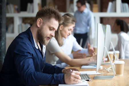 Focused businessman smart worker company member make notes writing on textbook working using computer internet program. Serious employee or student studying online learning course preparing for test