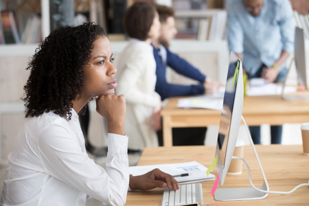 Diverse people in office area, focus on pensive african employee woman sitting at desk in front of pc, thinking analyzing market. Puzzled biracial worker having doubts trying to solve business problem