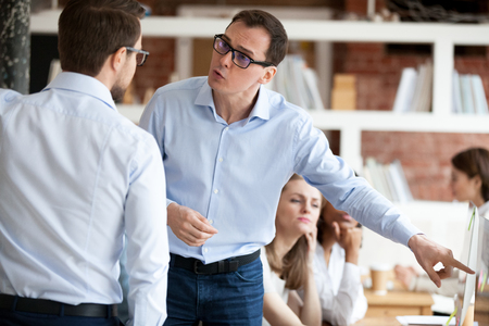 Indignant men colleagues quarrelling in shared office, having different opinion and disagreements arguing at work. Mad millennial employee accusing business partner disputing at coworking modern room