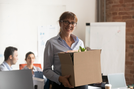 Smiling middle aged businesswoman in glasses just hired by company holding box looking at camera on first day at work, happy mature new female employee standing in modern office with belongings, portrait Stock Photo - 118055519