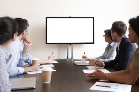 Gruppe von Führungskräften, die am Konferenztisch sitzt und auf einen weißen, leeren Mockup-TV-Bildschirm an der Wand schaut und eine Präsentation im Besprechungsraum beobachtet, ein Seminar des Unternehmensteams im Sitzungssaal Standard-Bild