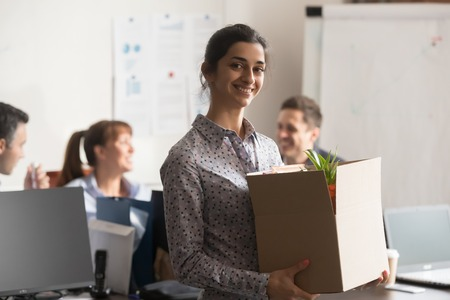 Portrait of new indian female employee or intern holding cardboard box starting job in modern company office, happy smiling hindu woman newcomer worker looking at camera on first day at work concept