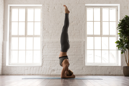 Young attractive woman practicing yoga, standing in headstand pose, salamba sirsasana exercise, beautiful girl in grey sportswear, leggings and bra working out at home or in yoga studio