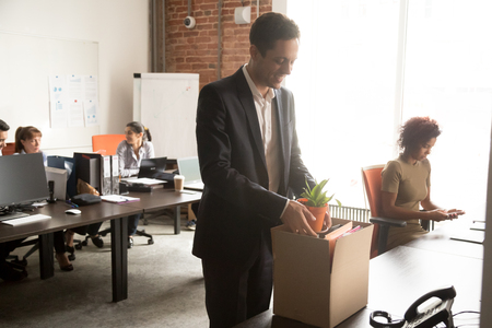 Happy young new male worker unpacking cardboard box at workplace in modern office, smiling millennial newcomer businessman employee starts job in company with belongings on first day at work concept Stock Photo - 118057825