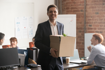 Cheerful smiling male employee manager in suit holding cardboard box with belongings looking at camera, happy business man worker newcomer standing in office starting work on first day at job concept Stock Photo