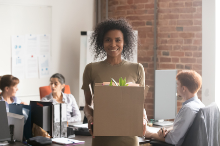 Happy young african female employee intern holding cardboard box looking at camera in modern office, smiling mixed race newcomer woman worker got new job posing on first day of work concept, portrait Stock Photo