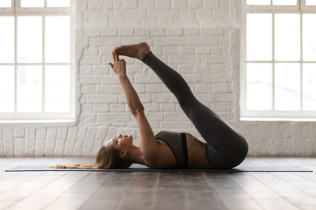 Sporty young woman in grey sportswear, pants and bra practicing yoga at home or in yoga studio, beautiful girl doing Double Leg Lift exercise, Urdhva Prasarita Padasana ppse, woking out Stock fotó