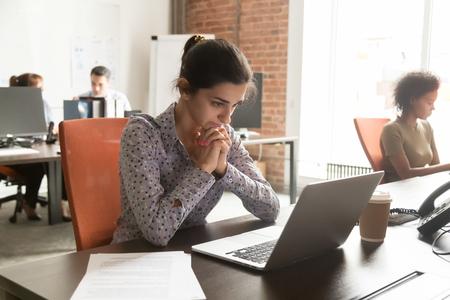 Verwirrte nachdenkliche indische Geschäftsfrau, die an eine Online-Problemlösung mit Blick auf den Laptop denkt, fokussierter hinduistischer Mitarbeiter, der über schwierige Computerarbeit am Arbeitsplatz in einem modernen Büro besorgt ist