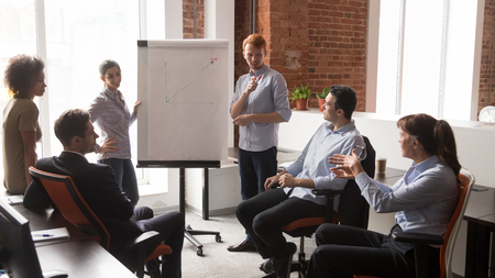 Confident diverse business managers coach speaker give corporate flip chart presentation consulting training employees group, mentor leader explaining discussing graph at office team meeting workshop Stock Photo