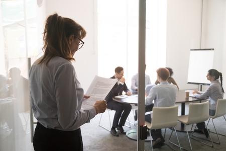 Gestresste nervöse, stotternde, unerfahrene Geschäftsfrau, die an der Bürotür steht und Angst vor der Leistung des Lesens von Papier hat, die Geschäftsrede vorbereitet, Angst vor Angstkonzept in der Öffentlichkeit